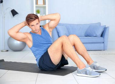 Young man doing exercises on rug in room
