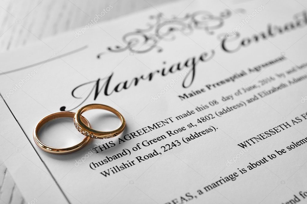 Golden Wedding Rings On Marriage Contract Closeup  Stock Photo