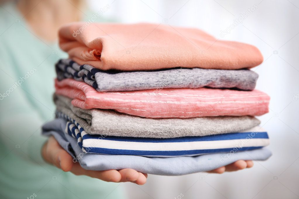 woman holding folded clothes in hands closeup � stock