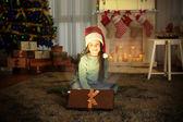Fényképek Aranyos kislány Santa kalap a karácsonyi ajándék otthon