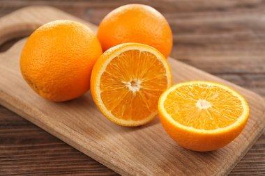 Fresh oranges on cutting board