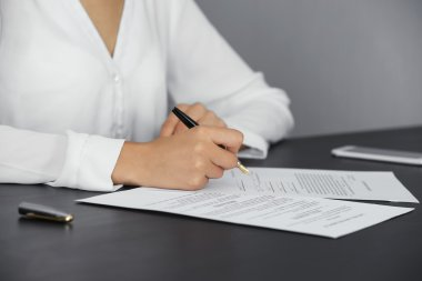 Woman signing last will and testament, closeup