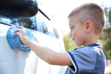 Small boy washing car with sponge on street