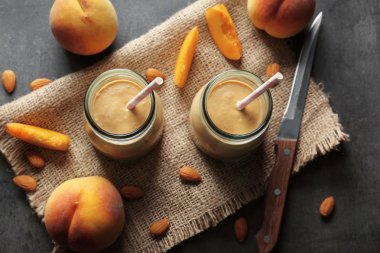 Mason jars with smoothie, peaches and napkin on grey table