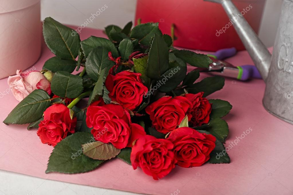 Beautiful red roses and wrapping paper on blurred background