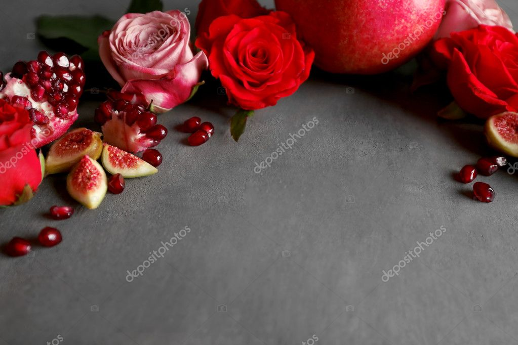 Composition of roses, figs and pomegranate pieces on grey textured background