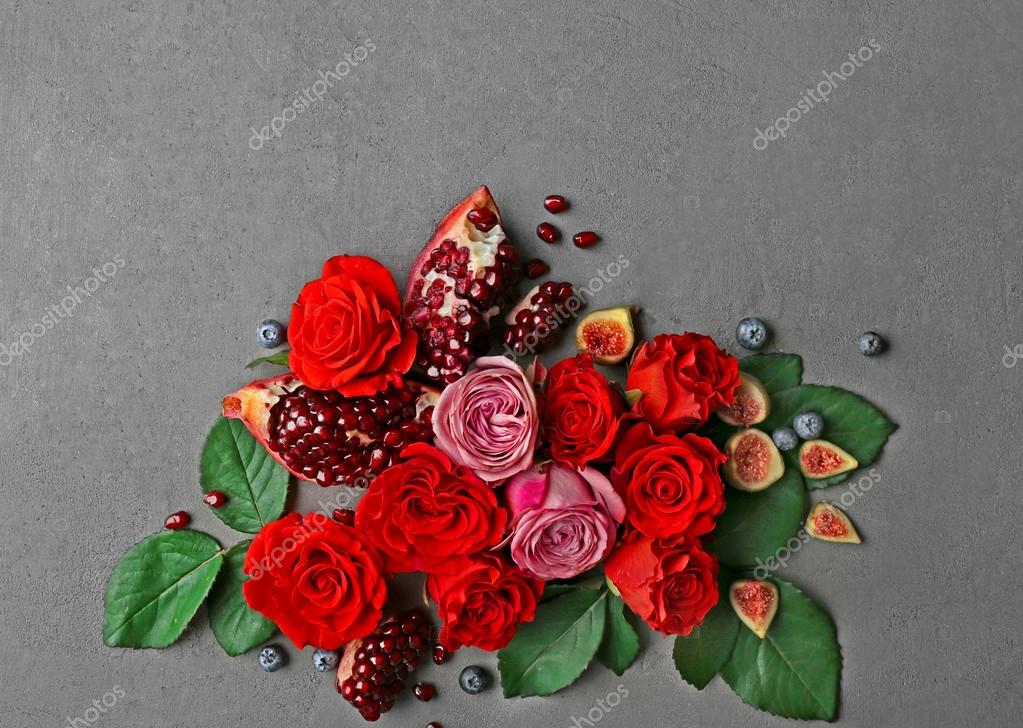 Composition of roses, figs, blueberries and pomegranate pieces on grey textured background