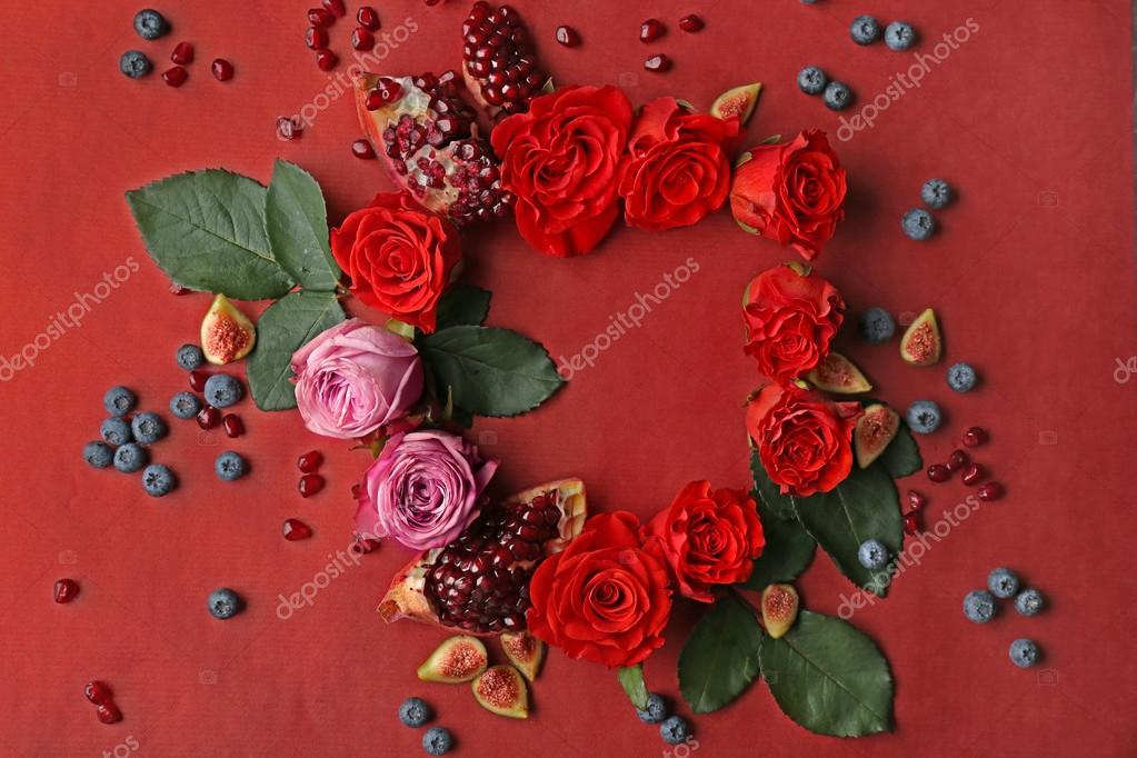 Composition of roses, figs, blueberries and pomegranate pieces on red background