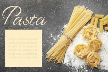 Different pasta with flour on gray table. Italian food concept. Word PASTA on background.