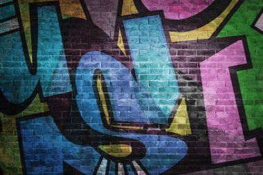 Colorful graffiti letters on brick wall background