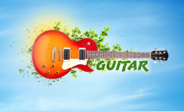 Creative art work concept. Electric guitar with green branches on sky background