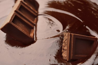 Delicious melted chocolate with pieces, closeup