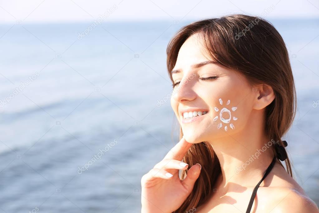 Jeune femme avec un écran solaire sur le visage, fond de la mer — Image de  belchonock 6f09d4a43da