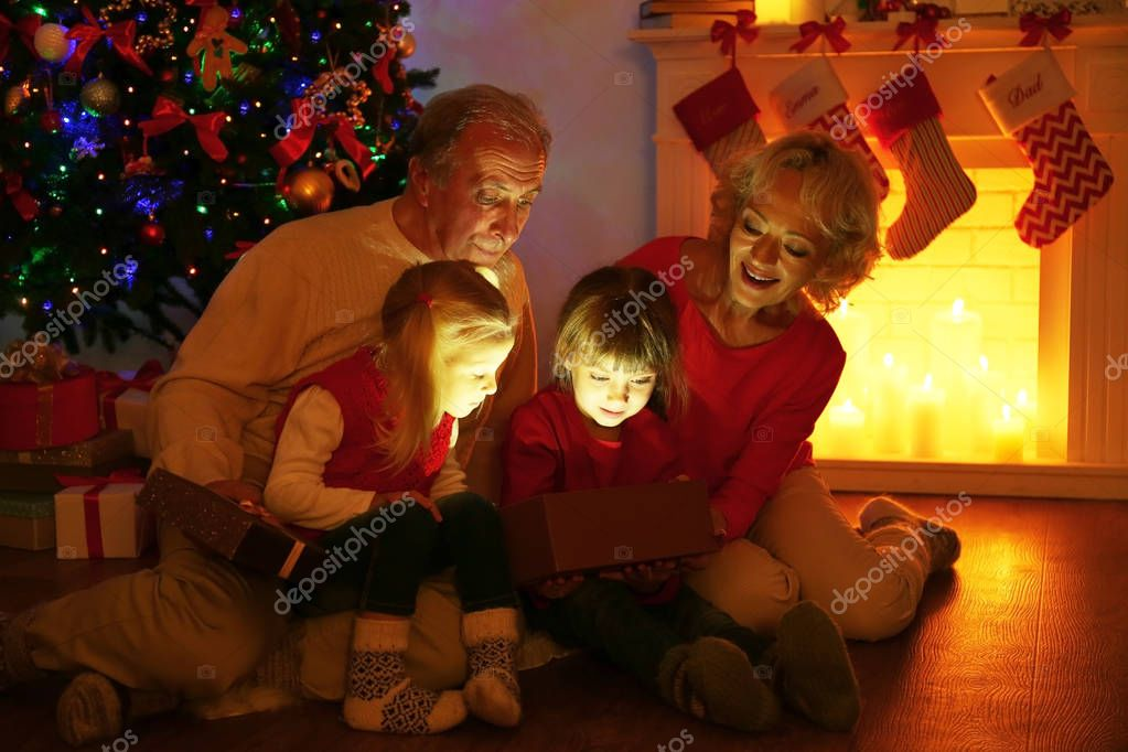 Älteres Ehepaar Mit Ihren Enkelinnen Weihnachtsgeschenk Kamin Öffnen ...