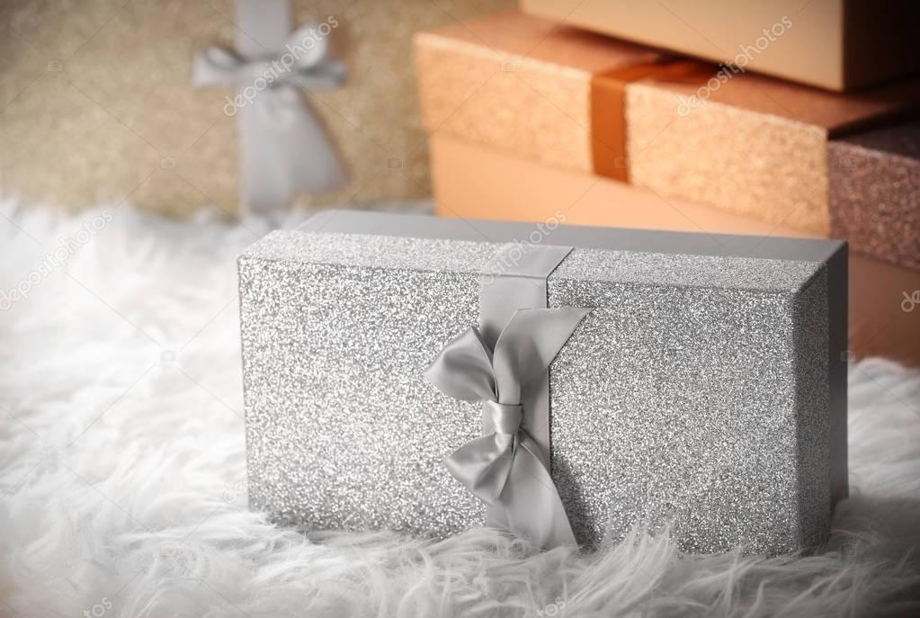 Christmas gifts in shining boxes on fluffy white carpet, closeup