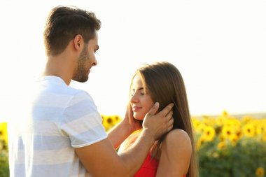 Romantic young couple embracing in a field of sunflowers