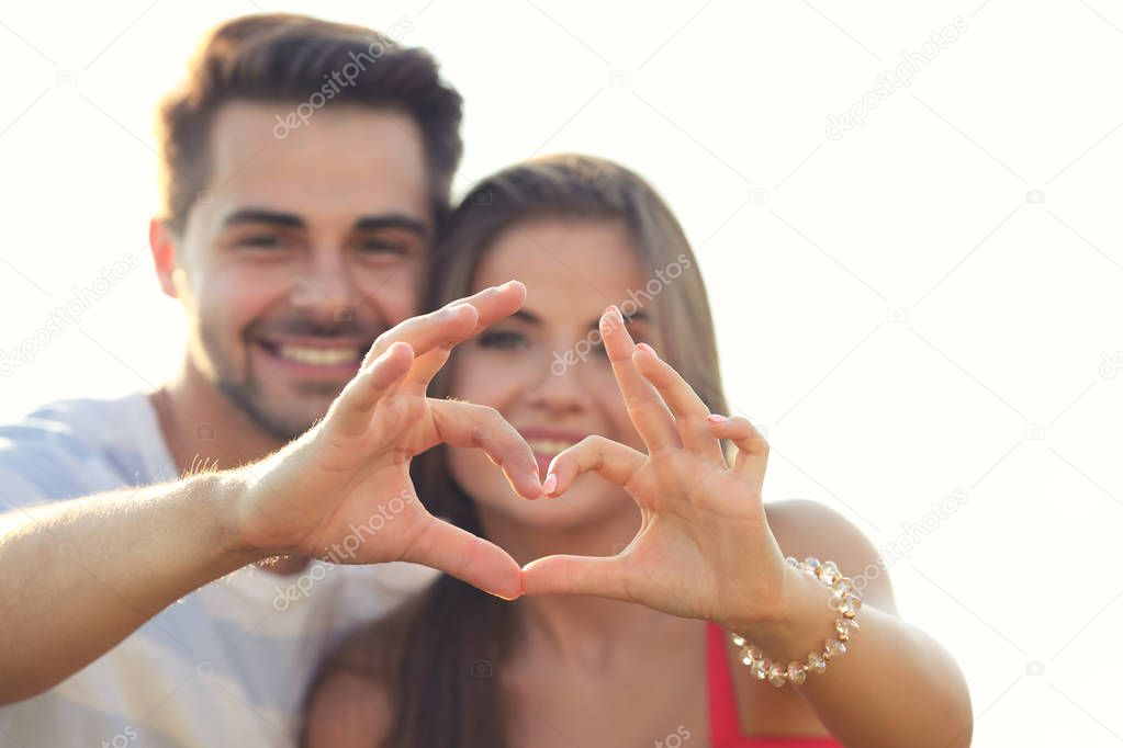 Happy young couple making heart shape with hands