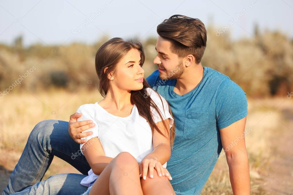 Beautiful young couple sitting together in a meadow
