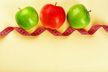 Dieting concept. Apples with measuring tape on light background