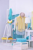 Photo Fashionable clothes hanging on rack at modern dressing room