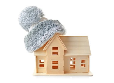 Plywood toy house with warm hat, isolated on white