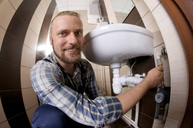 Handsome plumber repairing sink pipes in bathroom, close up view