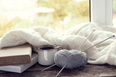 Hot drink with books, threads and plaid on windowsill