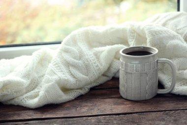 Hot drink with plaid on windowsill
