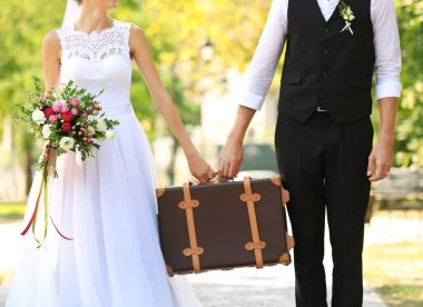 Groom and bride with vintage suitcase
