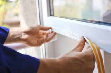 worker putting sealing foam tape on window