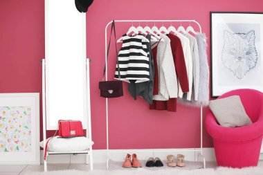 Fashionable clothes hanging on rack