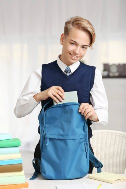 Schoolboy putting book
