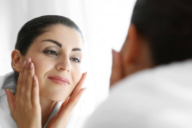 Adult woman checking her face