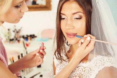 Wedding preparation. Professional makeup artist applying lip gloss on bride's lips