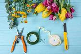 Krásné květiny a květinářství vybavení na modré dřevěné pozadí