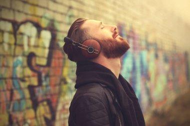 Handsome man in headphones listening to music outdoors