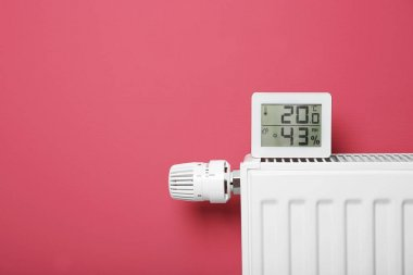 Electronic thermometer on heating battery and pink background