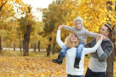Happy family playing in beautiful autumn park