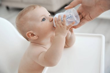 Mother giving to drink water baby from bottle, closeup
