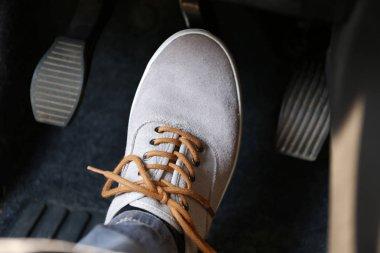 Human foot pressing car pedal