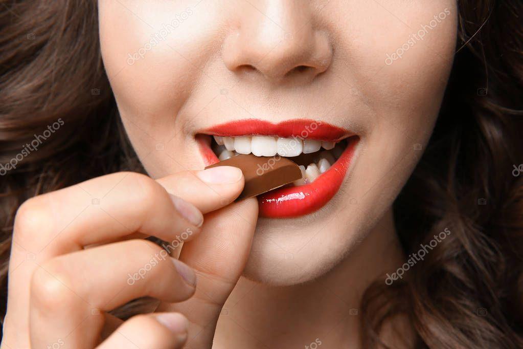 Girl eating chocolate, closeup