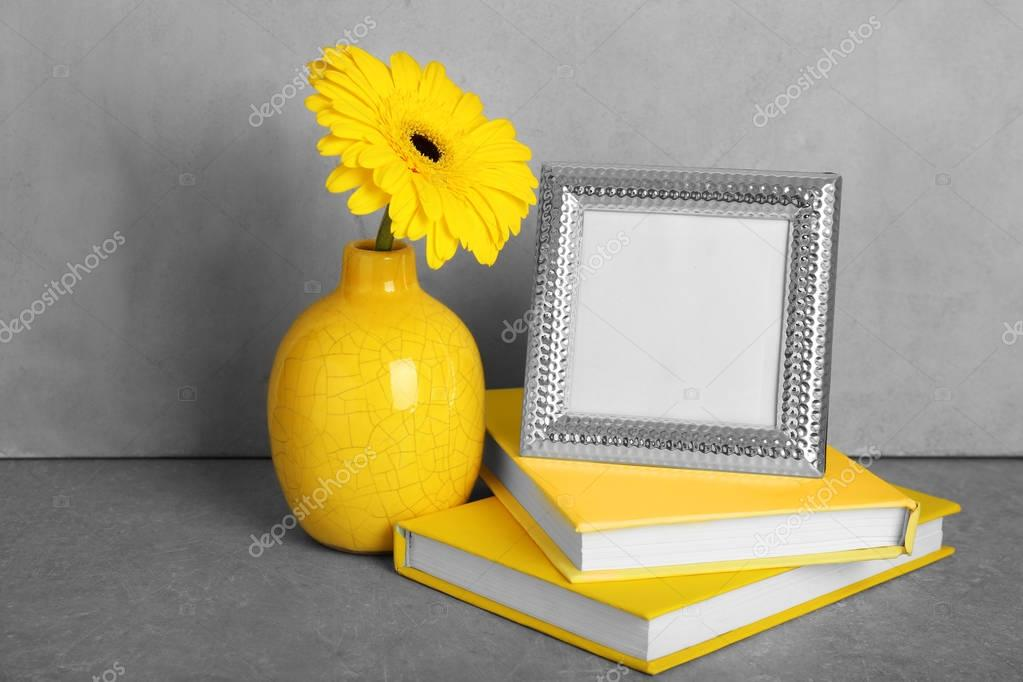 Yellow books, photo frame and vase with gerbera flower on grey background