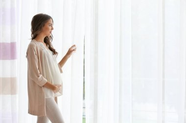 pregnant woman standing near window
