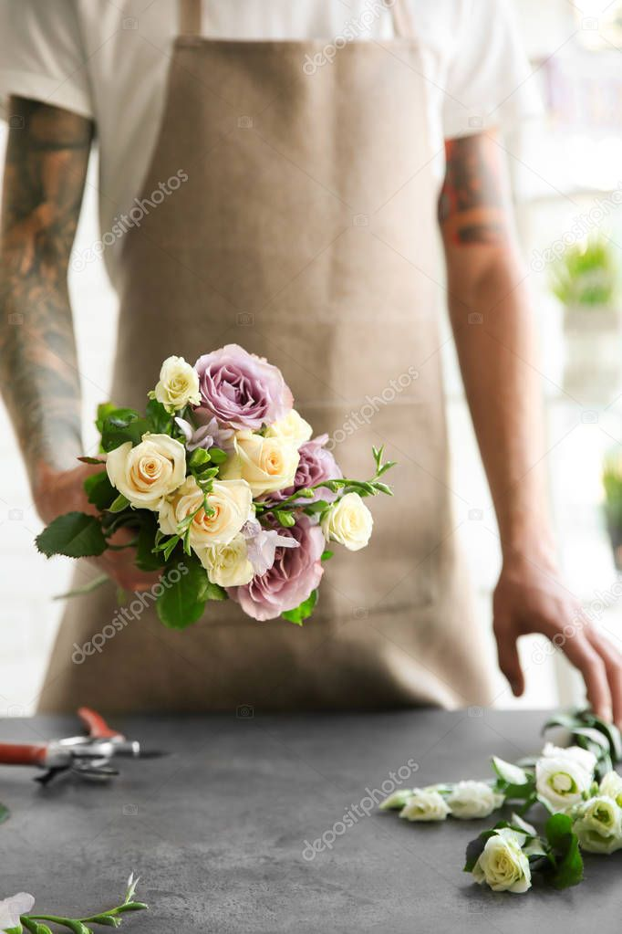 Male florist holding beautiful bouquet at flower shop