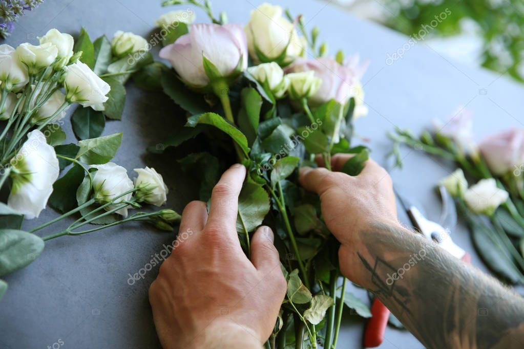 Male florist making bouquet at flower shop