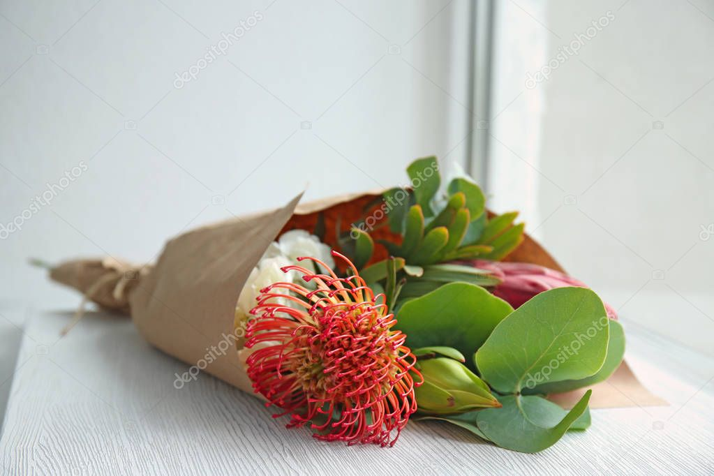 Beautiful bouquet of exotic flowers on windowsill