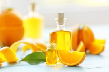 Two bottles with essential oil, orange slice, peel and leaf on wooden table