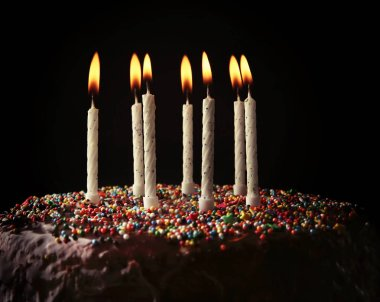 Birthday cake with colorful candles on dark background