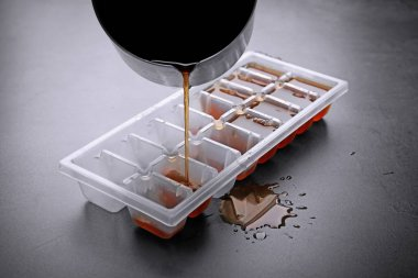 Pouring coffee in ice cube tray on grey background