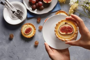 Female hand holding fig cake, top view